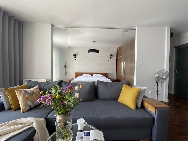 Wrocław Apartament Aravel Bianco - salon połączony z sypialnią, dekoracja świeżymi kwiatami